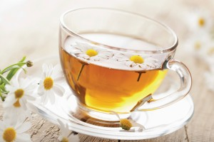 Glass mug of herbal tea with daisy flowers