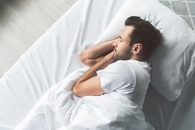 Cute young man sleeping on bed