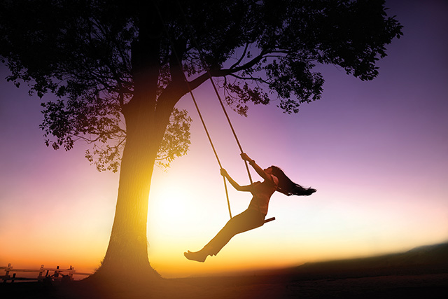 silhouette of young woman on a swing