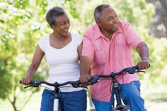 Older couple riding bikes in park